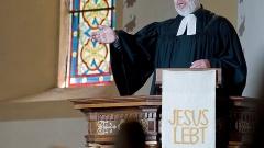 Pfarrer predigt auf der Kanzel.