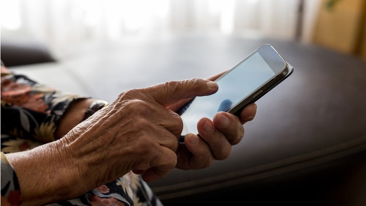 Eine alte Frau wählt eine Nummer auf einem Mobiltelefon.