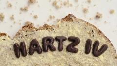 """Schriftzug """"Hartz IV"""" aus Schokoladenbuchstaben auf einem Butterbrot"""