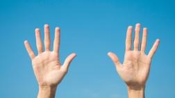 Zehn Finger hochgestreckt vor blauem Himmel.