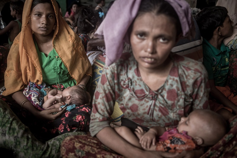 Zwei Rohingya Flüchtinge. Beide halten Babies in den Händen und sehen erschöpft in die Kamera