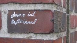 Schrift auf einer Steinmauer: Anna ist lesbisch - wobei das Wort lesbisch mit ß und ss falsch geschrieben ist.