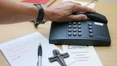 Telefon, Stift, Papier und ein Kreuz auf einem Tisch