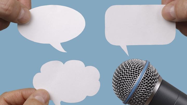 Sprechblasen aus Papier vor einem Mikrofon.