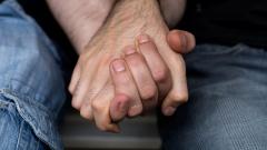 Zwei Männer halten sich an den Händen. Nahaufnahme.