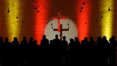 Chor steht in einem farbig beleuchteten Altarraum einer Kirche.