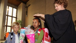 Pfarrerin Pia Baumann von der evangelischen St. Jakobsgemeinde in Frankfurt-Bockenheim segnet bei einem ökumenischen Einschulungsgottesdienst in der katholischen St. Elisabeth Kirche in Frankfurt-Bockenheim am Schulanfänger.