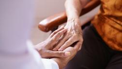 Ein junger Mensch hält die Hand eines alten Menschen.