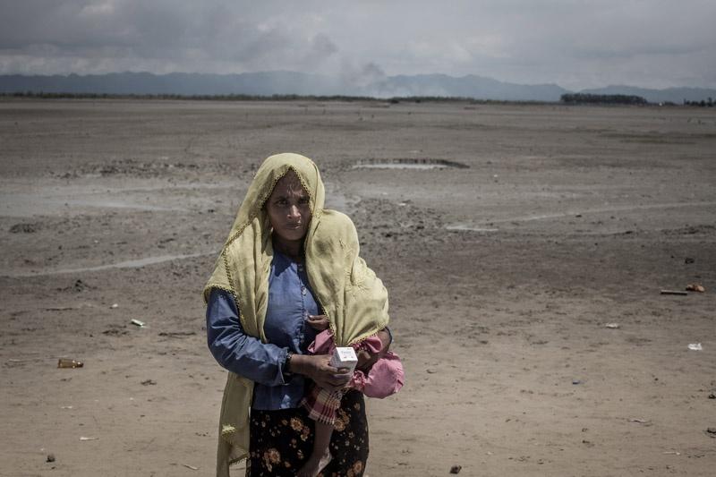 Eine Rohingya-Frau mit Kopftuch und Kind auf der Schulter steht in einer öden Ebene und blickt in die Kamera.