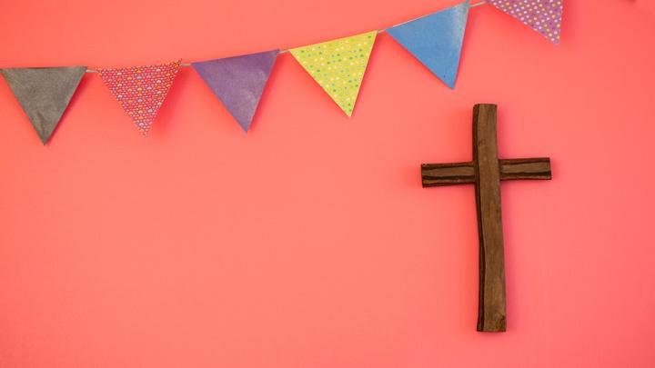 Eine bunte Wimpelkette hängt über einem Holzkreuz an der Wand.