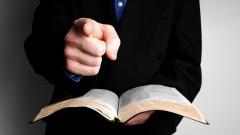 Ein Mann hält die Holy Bible in eine Hand und zeigt mit dem Zeigfinger der anderen Hand auf den Betrachter.