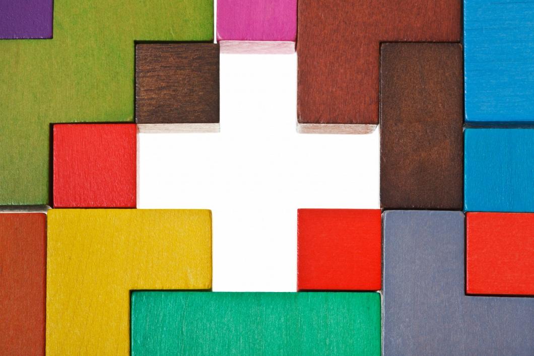 Zwischen bunten Bauklötzen ist ein Leerraum in Form eines Kreuzes.