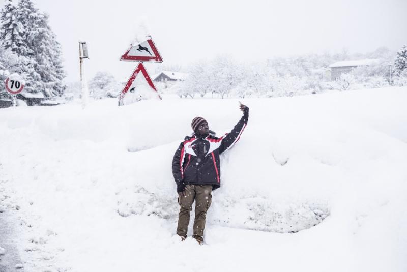 Ein dunkelhäutiger junger Mann schießt ein Selfie vor einer Schneeanhäufung.