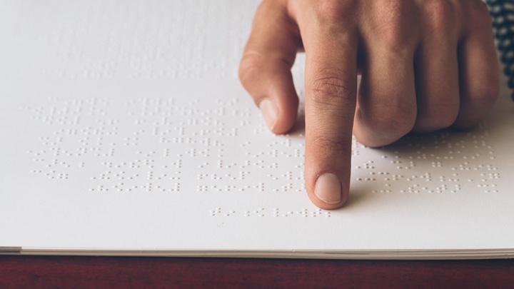 Hand auf einer Buchseite mit Punktschrift.