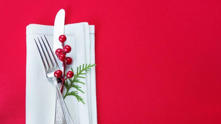 Messer und Gabel liegen auf einer weihnachtlich gedekten Tafel.