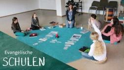 Kinder beim Unterricht auf blauem Teppich