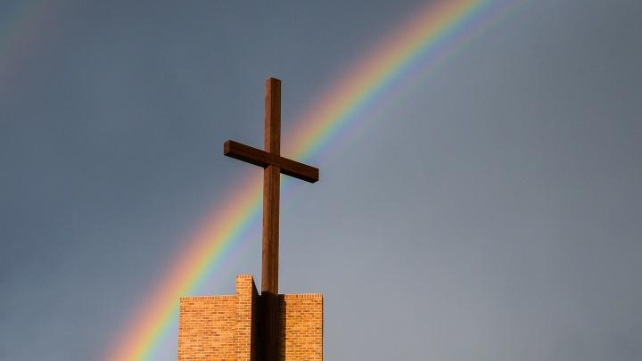 Regenbogen über einem Kirchturm.