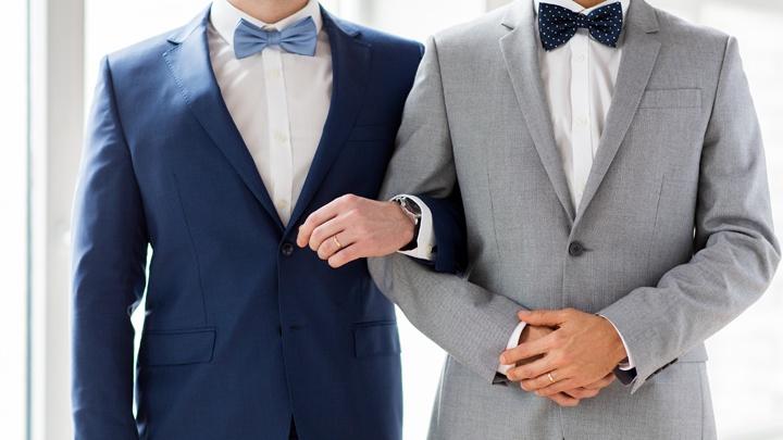 Homosexuelles Pärchen, das untergehakt nebeneinander steht.
