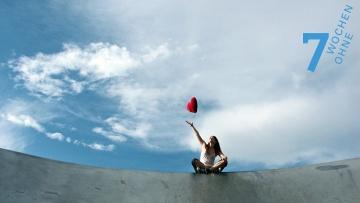 Eine junge Frau sitzt auf einer Mauer und wirft ein rotes Plüschherz in den Himmel.