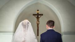 Brautpaar steht in der kirche vor einem Kruzifix.