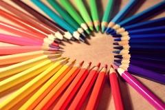 Herz aus verschieden farbigen Buntstiften.