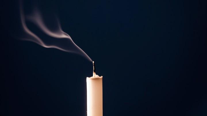 Rauch steigt von dem erloschenen Docht einr Kerze auf.