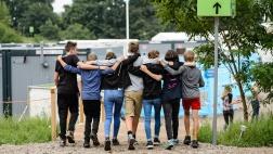 Jugendliche des Konfirmanden-Zeltlagers in Wittenberg gehen Arm in Arm über das Gelände.