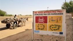 Ein Schild warnt in der Wüstenstadt Timbuktu in Mali vor versteckten Granaten und Minen (Archiv).