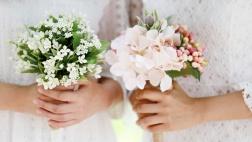 Nahaufnahme zweier Bräute mit ihren Brautsträußen.
