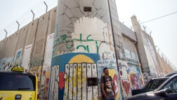 Ein Mann lehnt gegen die Mauer, die durch Bethlehem verläuft.