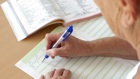 Ein Erwachsener übt, Buchstaben zu schreiben.
