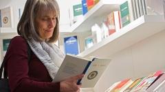 Eine Frau liest in der neuen Bibel am Stand der Deutschen Bibelgesellschaft auf Frankfurter Buchmesse.