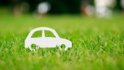 Ein aus Papier ausgeschnittenes Auto auf grünem Gras.