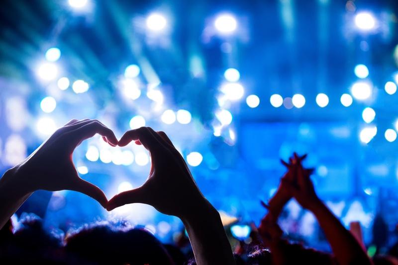 Konzertbesucher bilden mit ihrem Händen ein Herz