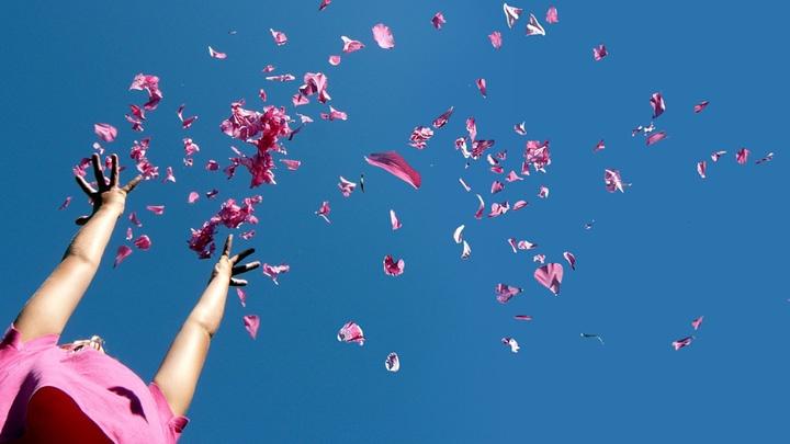 Frau wirft Blüttenblätter in die Luft.