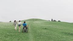 Zwei Frauen helfen einem Mann im Rollstuhl auf einem steilen Weg.
