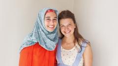 Eine Muslima und eine Christin stehen nebeneinander und lächeln in die Kamera.