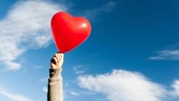 Hand mit Luftballon in Herzform vor blauem Himmel.