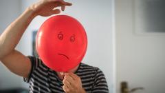 Ein Mann hält einen roten Luftballon, auf den trauriges Gesicht gemalt ist, vor seinen Kopf.