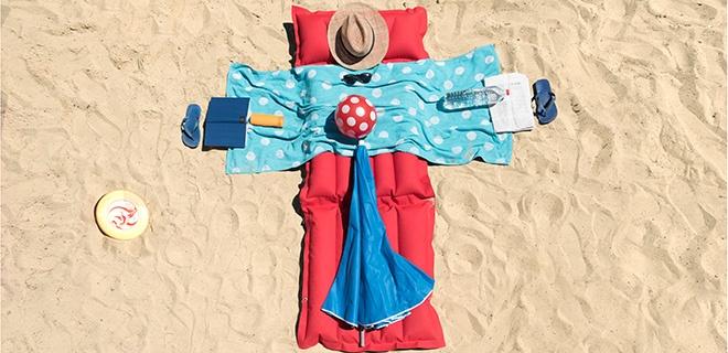 Kreuz aus Handtüchern am Strand