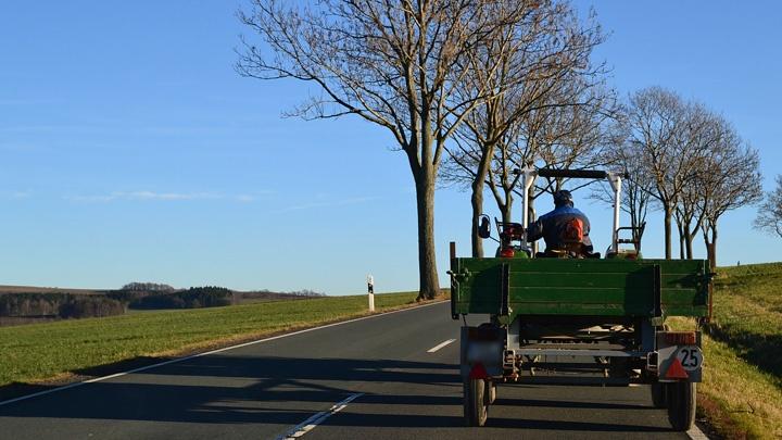 Ein Traktor fährt auf einer Bundesstraße.