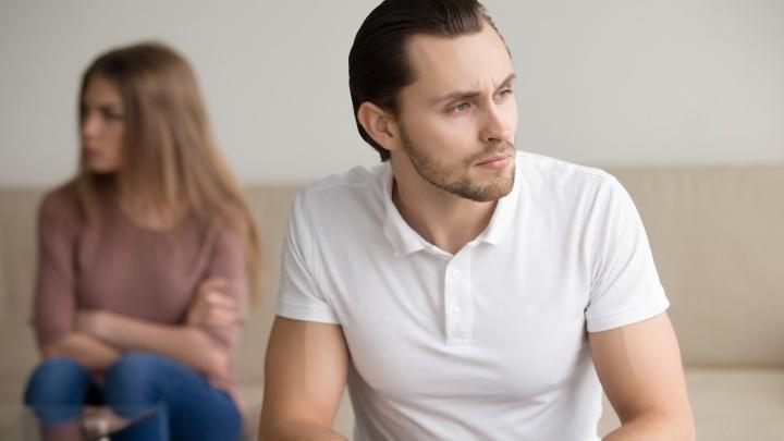 Ein junges Paar sitzt nachdenklich, schweigend auf einer Couch