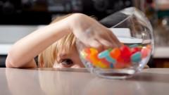 Ein Junge greift in ein Glas mit Süßigkeiten.