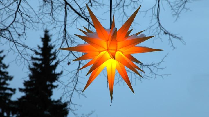 Leuchtender Herrnhuter Weihnachtsstern in der Abenddämmerung