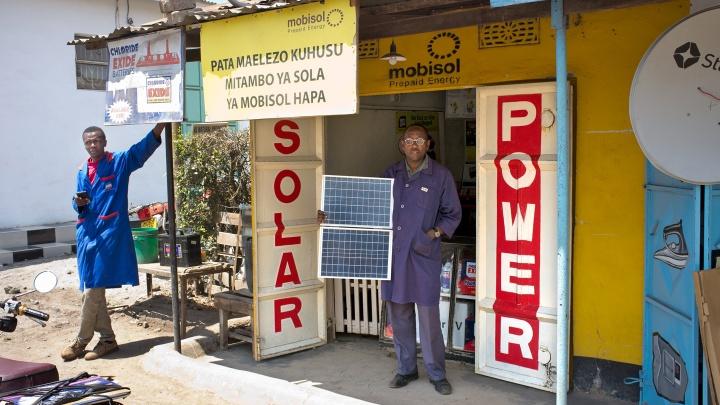 Frank Evans mit Solarzellen vor seinem Elektronikladen an der Strasse von Arusha nach Moshi im Norden von Tansania.