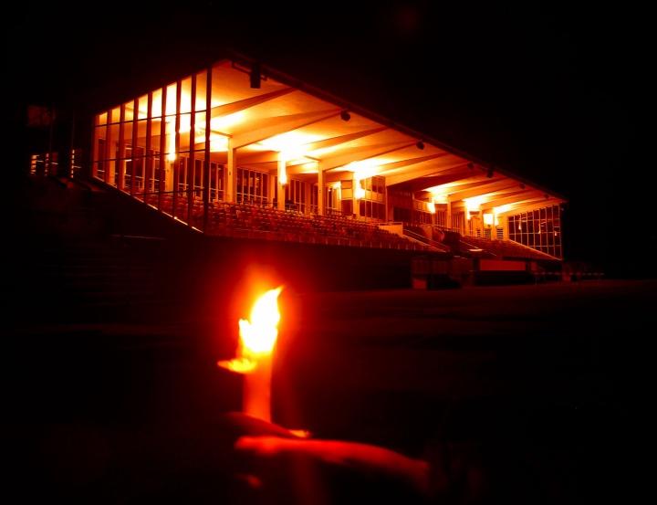 Schweinfurter Willy-Sachs-Stadion beleuchtet, im Vordergrund eine Hand, die eine Kerze hält.