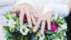 Zwei Bräute halten ihre Hände mit Eheringen über ihren Brautsträußen.