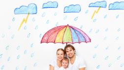 Vater, Mutter und Kleinkind sitzen vor einer Wand, auf die ein bunter Regenschirm und Regenwolken gemalt sind.