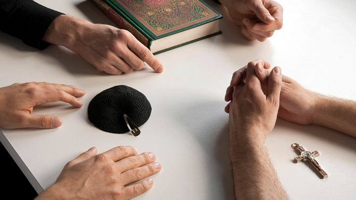 Symbole für die drei monotheistischen Weltreligionen Christentum, Judentum und Islam: Kreuz, Kipa und Koran.