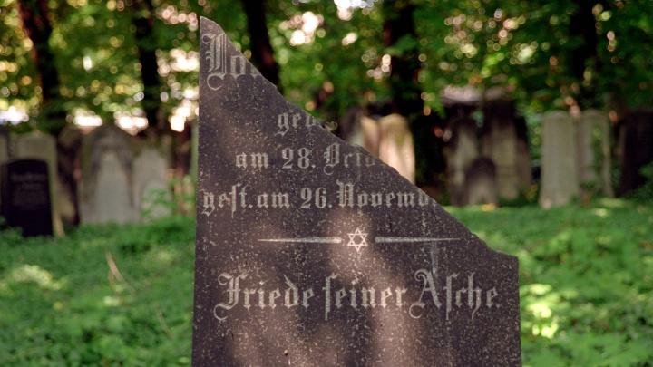 """Zerbrochener jüdischer Grabstein mit dem Schriftzug """"Friede seiner Asche"""" am jüdischen Friedhof in Berlin-Prenzlauer Berg."""
